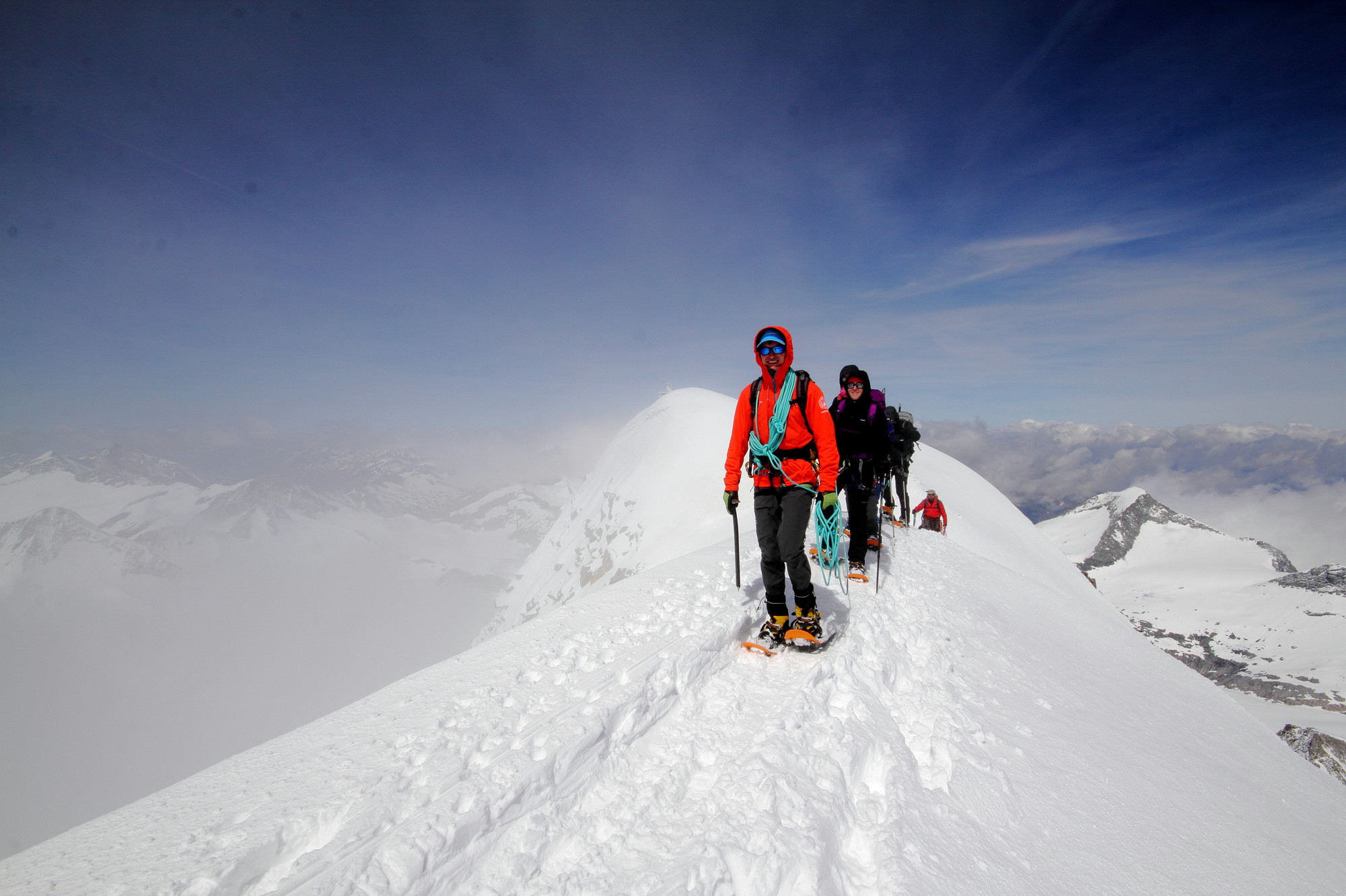 Schneeschuhwanderer gehen hintereinander einen Bergrücken entlang.