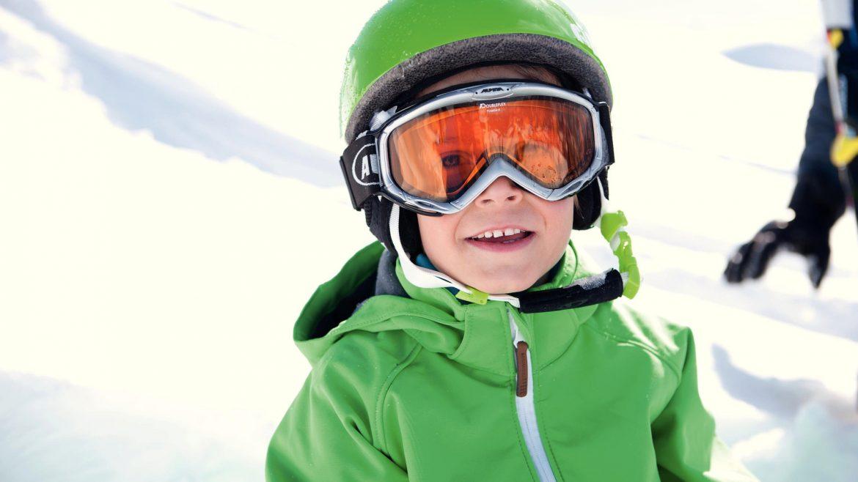 Bub mit grüner Jacke und grünem Helm hat sichtlich Spaß im Schnee
