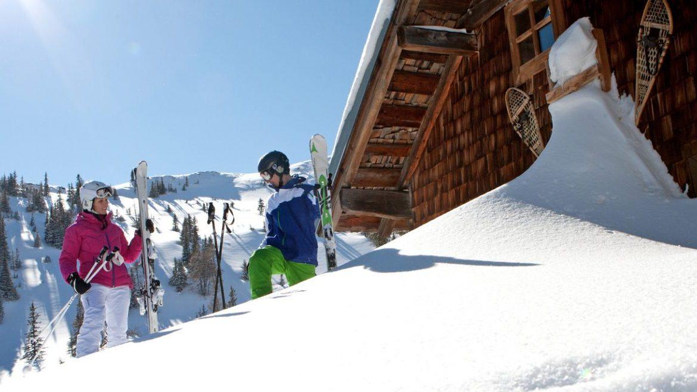 Skifahrer stehen vor einer tiefverschneiten Hütte in der Sonne