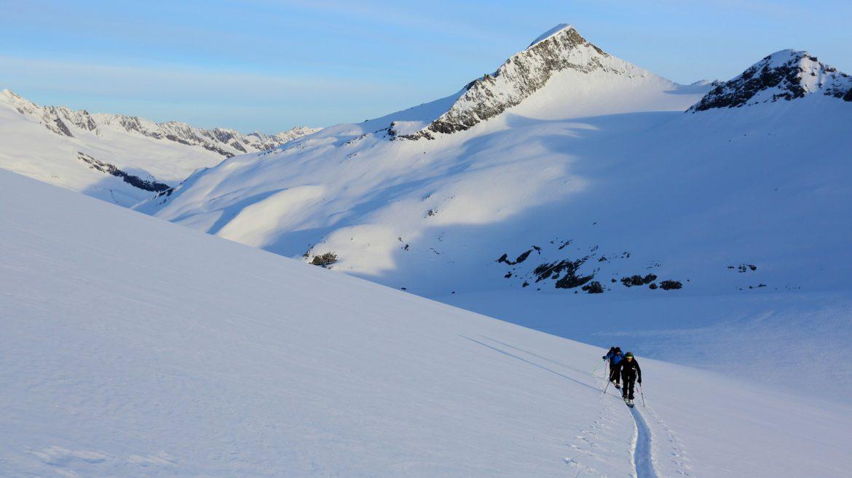 Skitourengeher ziehen eine gerade Spur durch den Tiefschnee des Großvenedigers.
