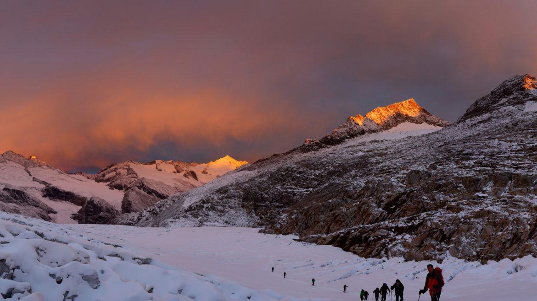 Eine Gruppen von Skitourengehern auf dem Weg nach oben im herrlichen Licht des Sonnenuntergangs.