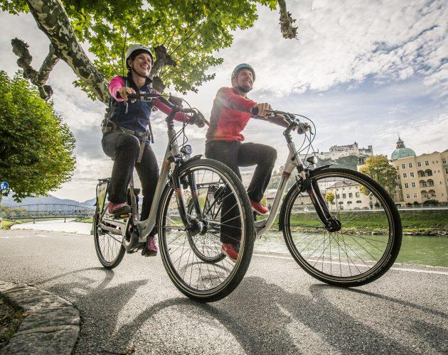 Zwei Radfahrer fahren am Ufer der Salzach auf dem Tauernradweg durch die Stadt Salzburg.