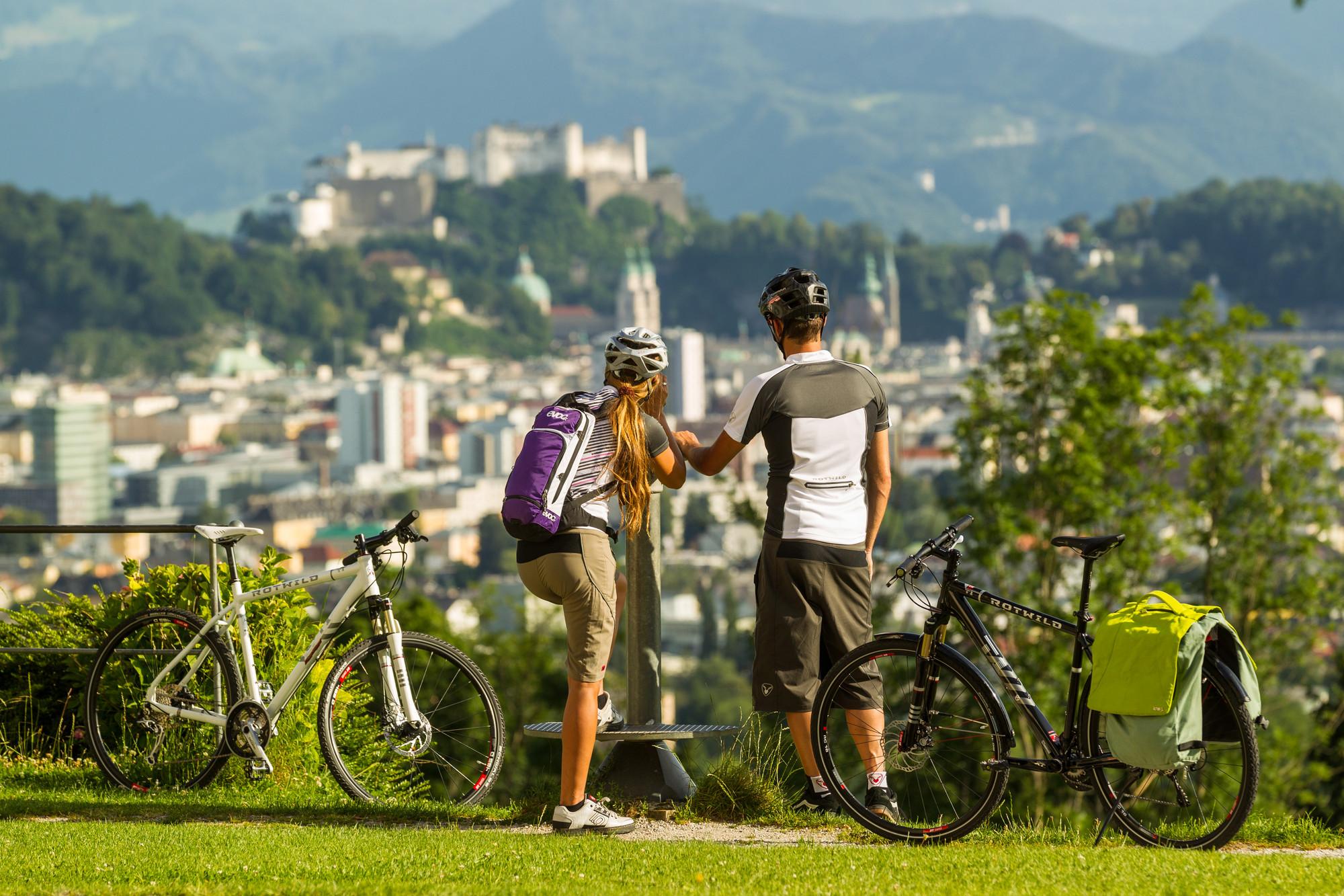 Ein Pärchen steht neben den Fahrrädern und genießt den imposanten Blick auf die Stadt Salzburg.