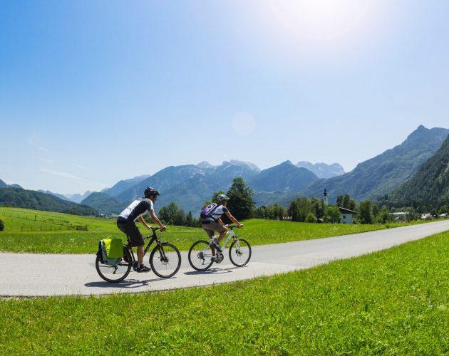 Zwei Radfahrer fahren über eine Straße am Tauernradweg vor herrlichem Bergpanorama.
