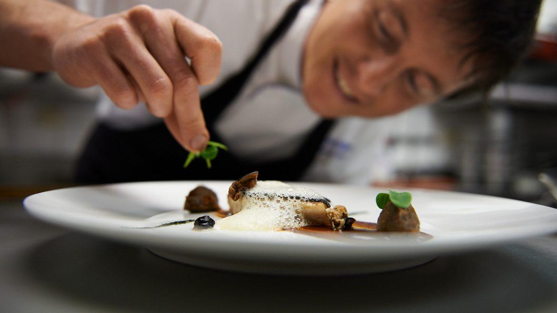 Haubenkoch garniert Essen mit Kräutern
