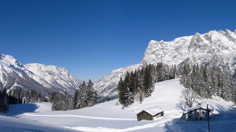 Verschneiter Stadl vor prächtiger Winterkulisse