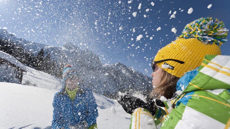 Frau in gelber Mütze pustet Schnee aus der Hand