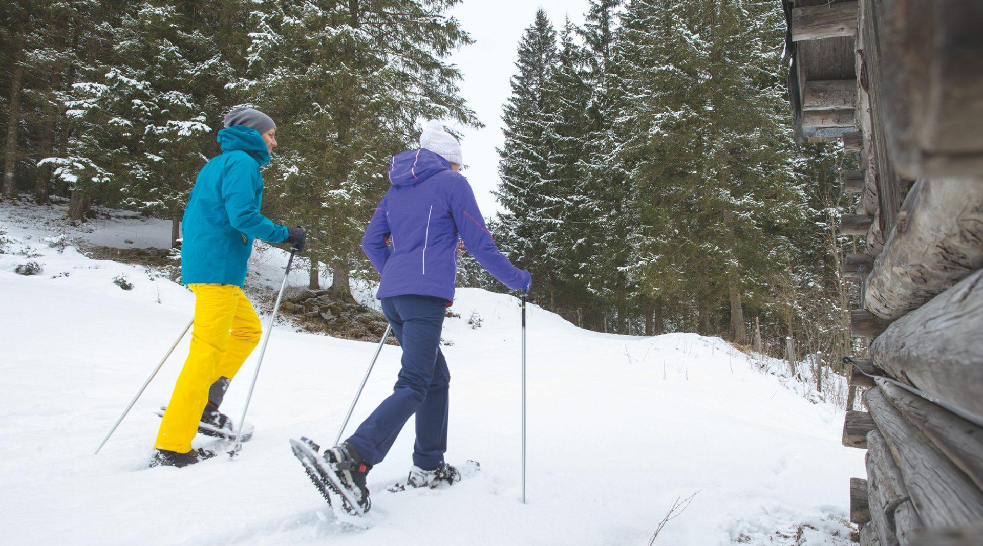 Paar wandert mit Schneeschuhen durch den verschneiten Wald