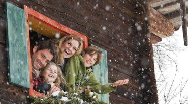 Familie beugt sich aus dem geöffneten Bauernhoffenster und freut sich über die Schneeflocken