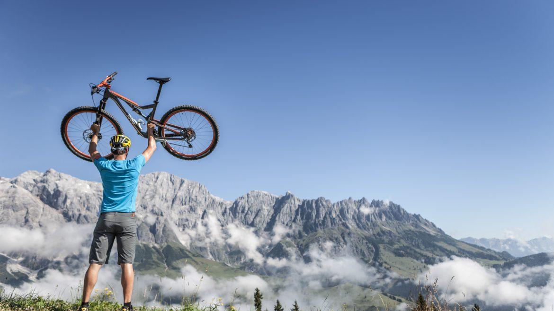 Biker stemmt vor der Kulisse des Hochkönigs sein Bike hoch.