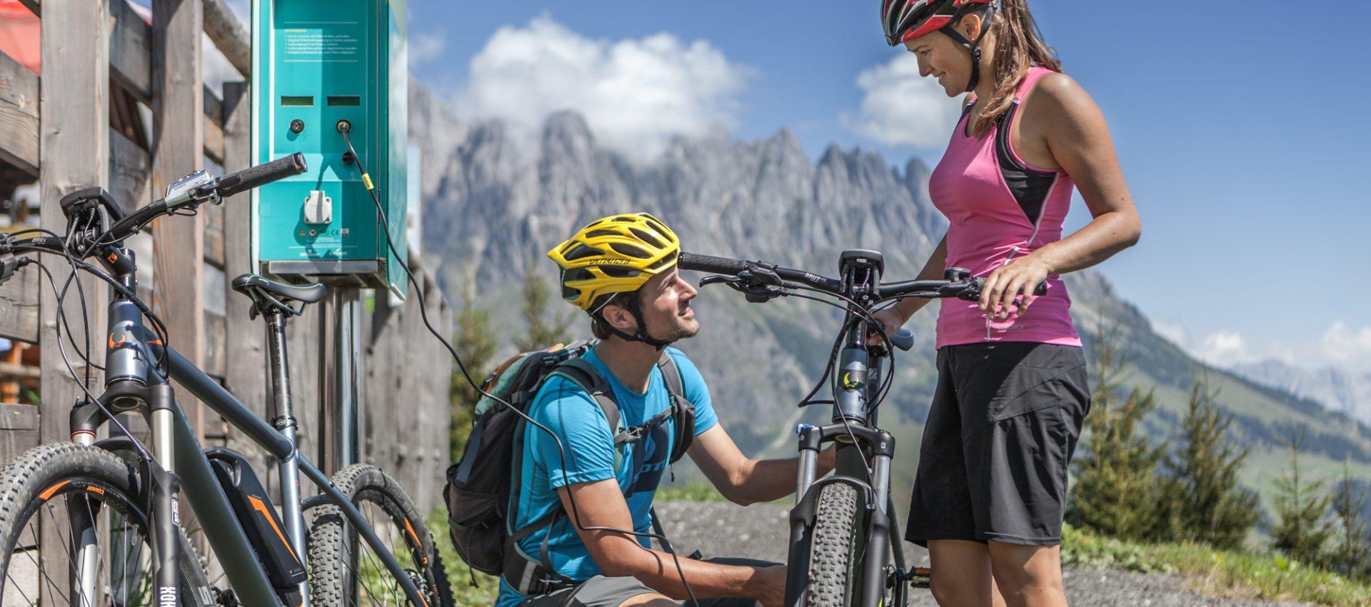 E-Biker tanken an einer E-Tankstelle auf.