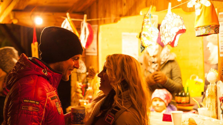 Pärchen mit Glühwein am Adventmarkt.