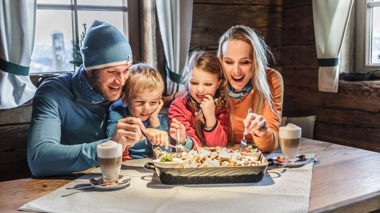 Familie genießt Kaiserschmarrn in der Skihütte.