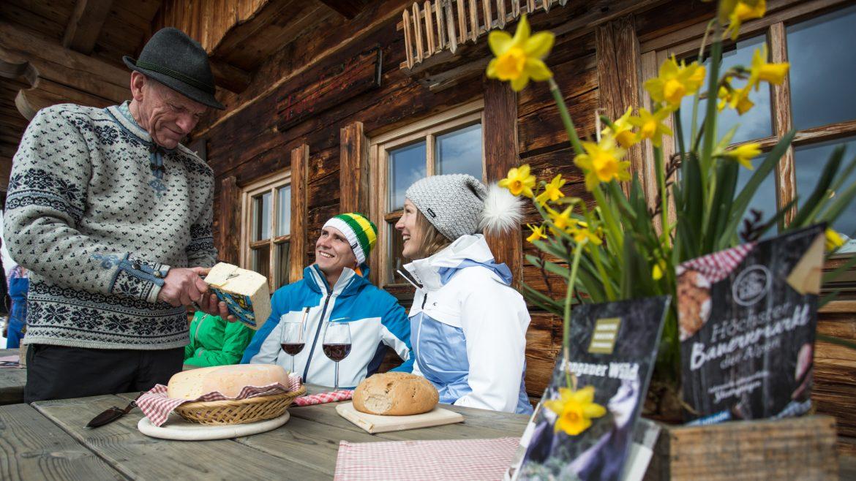 Pärchen vor der Hütte wird vom Hüttenwirt mit Käse bewirtet.
