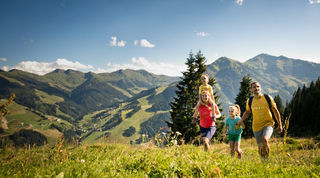 Familie wandert auf Blumenwiese.