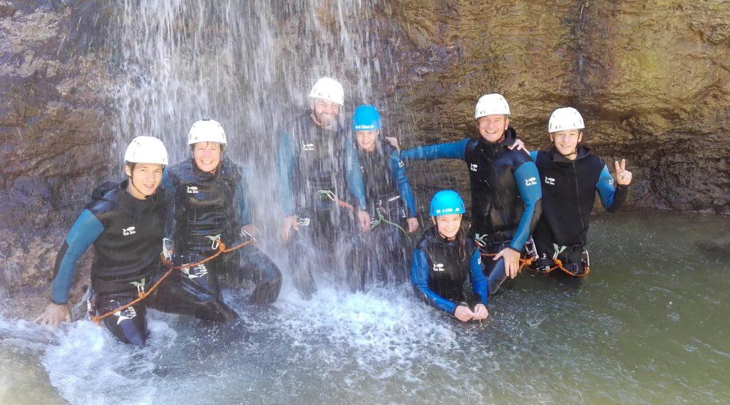 Gruppe beim Canyoning unterm Wasserfall.