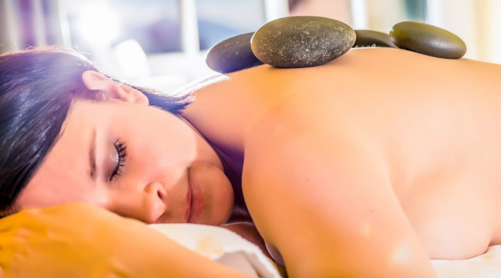 Massage: Frau mit heißen Steinen am Rücken