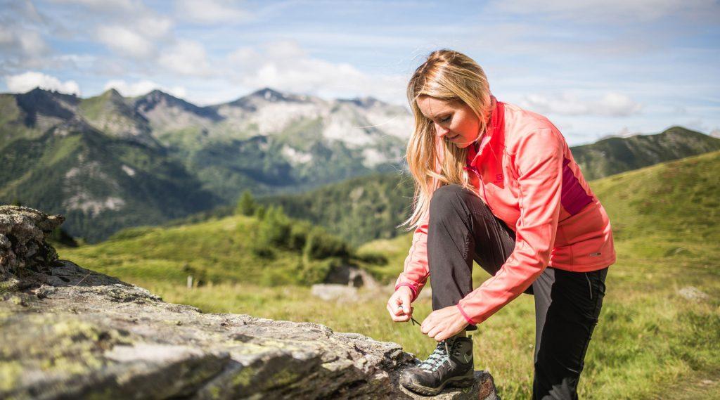 Frau in roter Jacke und schwarzer Wanderhose bindet sich die Schubändern
