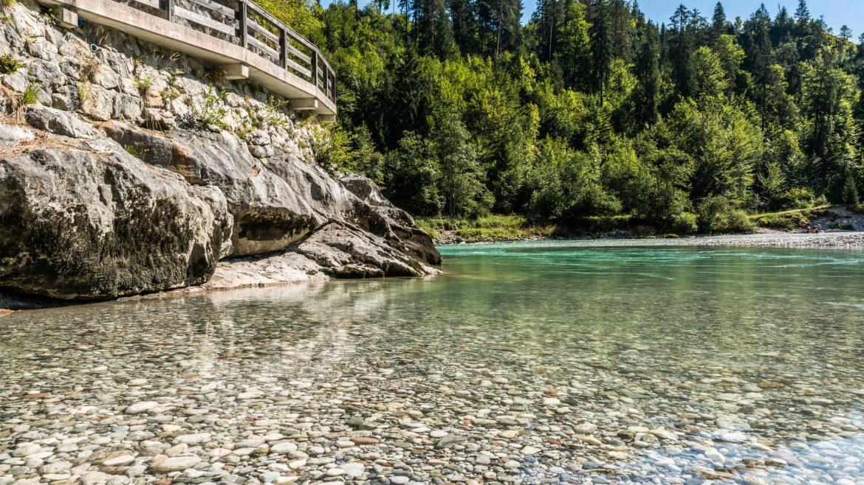 Ein Flussbett mit klarem Wasser und einer Brücke