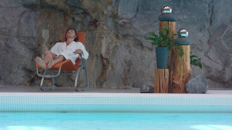 Mann entspannt in Liegestuhl am Beckenrand