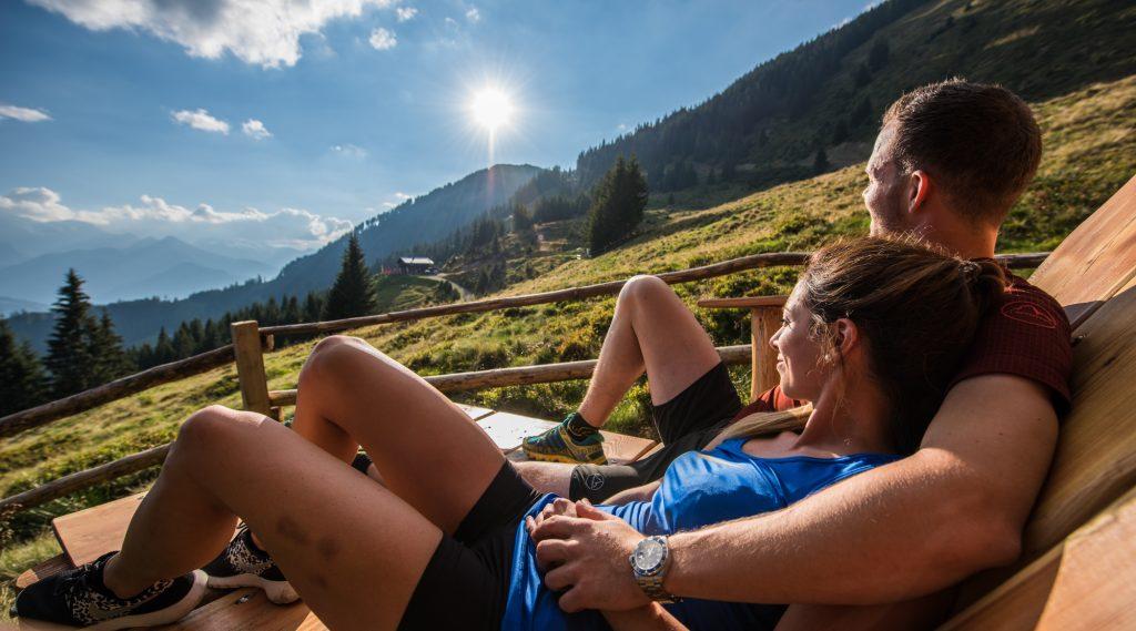 Paar liegt auf der Almwiese und genießt den Sonnenschein