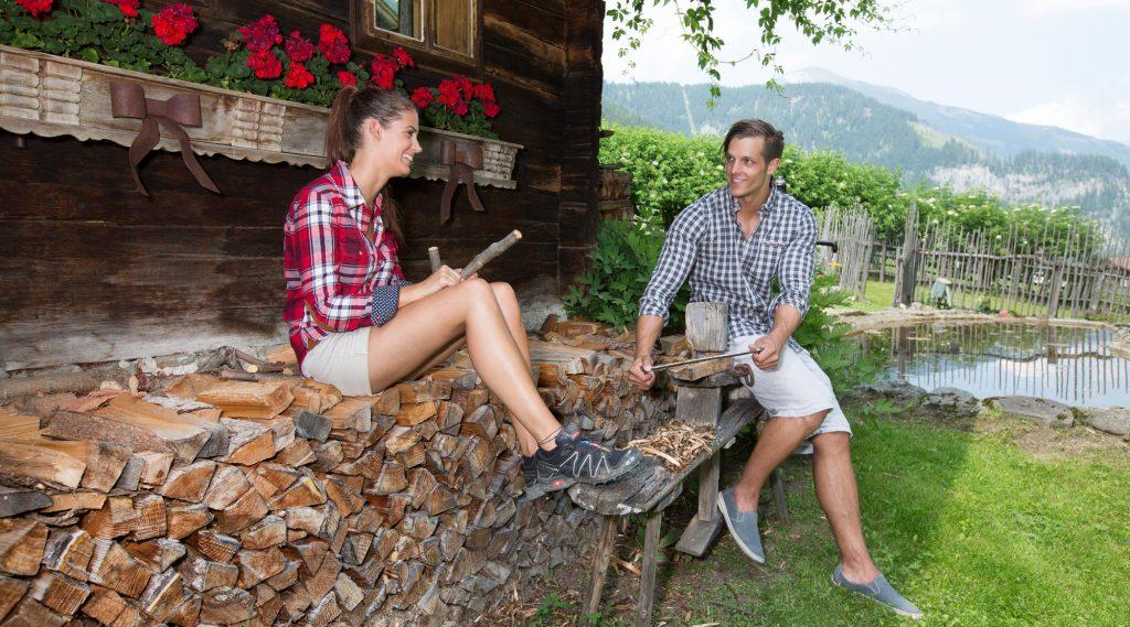 Junges Paar sitzt auf einem Holzstoß vor einer Hütte