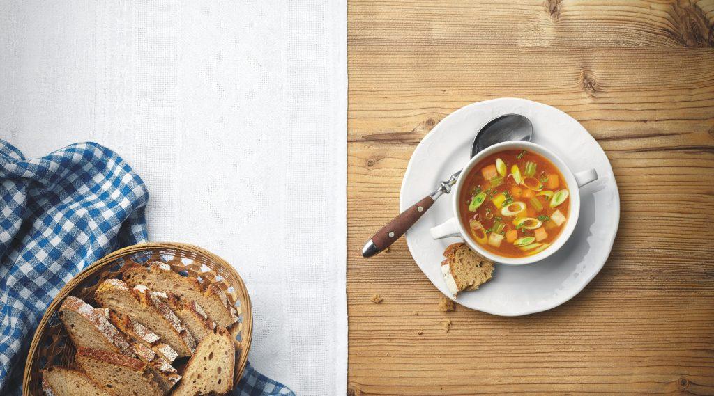 Heiße Suppe mit Gemüsegarnitur und Schwarzbrot am Holztisch mit weißer Tischdecke