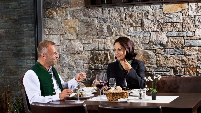 Paar isst im Restaurant und trinkt dazu Wein