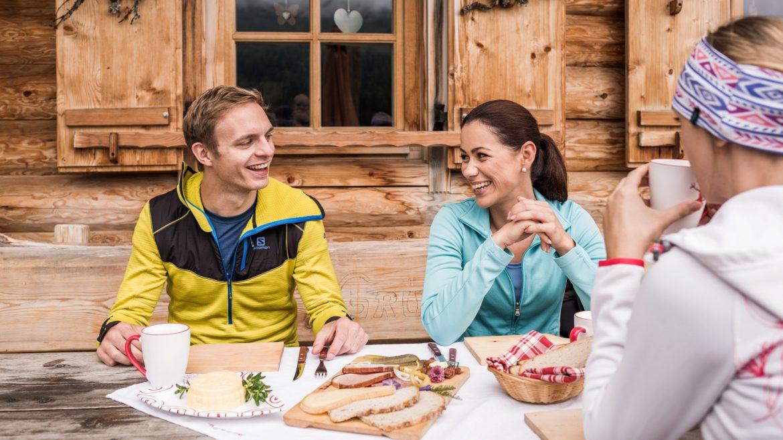 Mann und Frau lachen, bei der Almjause
