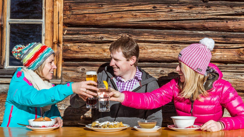 Mann und zwei Frauen sitzen in Wintergewand vor der Skihütte und stoßen an