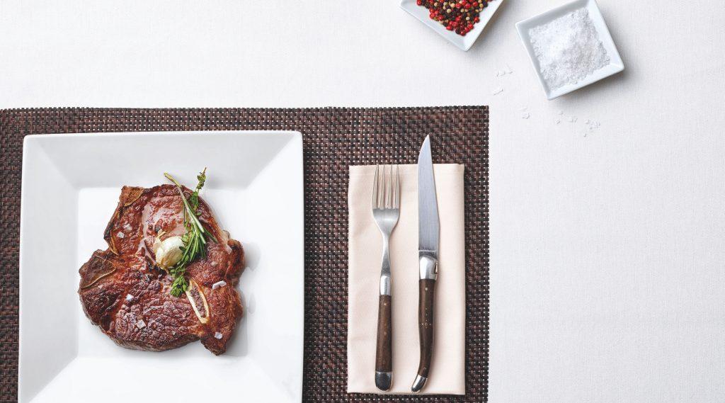 Festlich gedeckter Tisch mit Steak auf weißem Teller, Besteck und Beeren