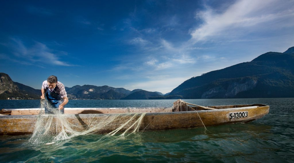 Man with fishing boat and fishing net in the lake