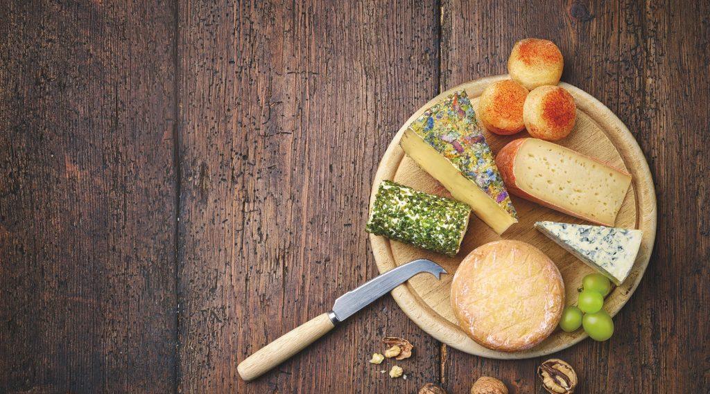 Käsesorten, diverse, am runden Holzbrett mit Garnitur und Messer auf Holztisch