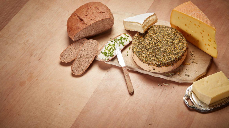 Verschiedene Käsesorten und Bauernbrot liegen neben einem Schnittlauchbrot mit Butter