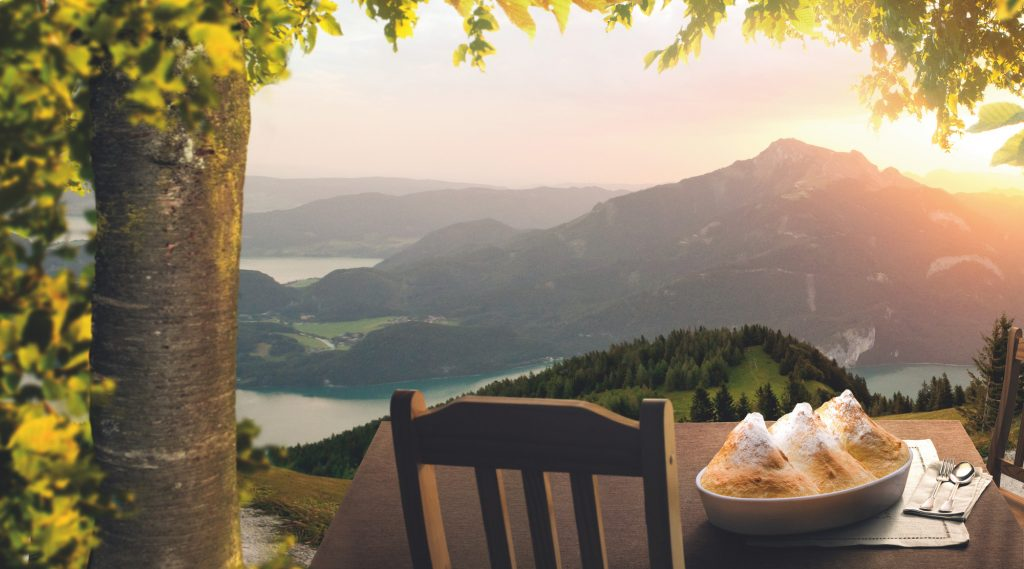 Salzburger Nockerl on a table with armchair on a mountain, in the distance a lake panorama