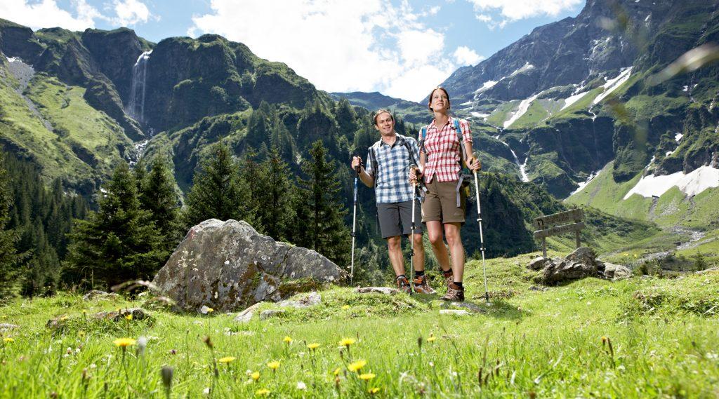 Paar in kurzen Hosenund karierten Hemden wandet über eine blühende Almwiese
