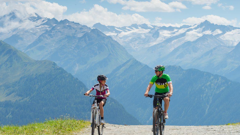 zwei Mountainbiker auf einer Schottestraße, im Hintergrund hohe Berge