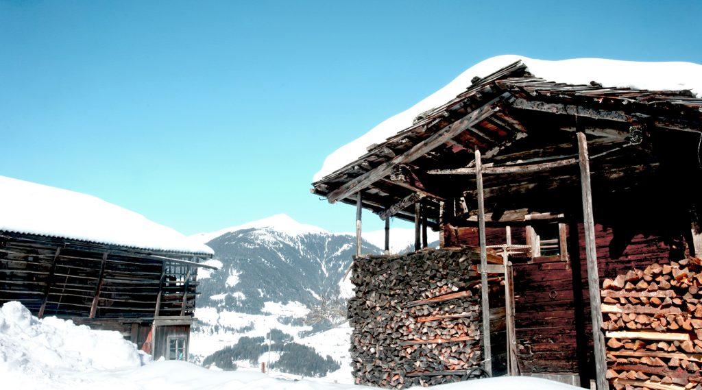 Schneebedeckte Holzhütte mit aufgeschichtetem Holz