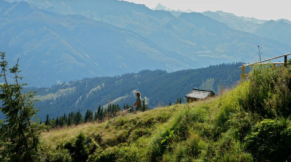 Wanderer auf Alm, links im Hintergrund ist das Dach einer Almhütte sichtbar