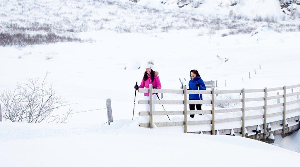 Zwei Frauen in pinker und blauer Jacke beim Winterwandern