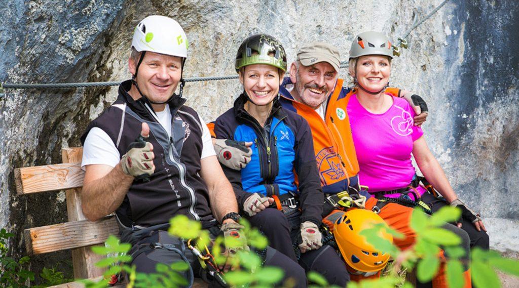 Kletterer mit Helmen stehen an einer Kletterwand