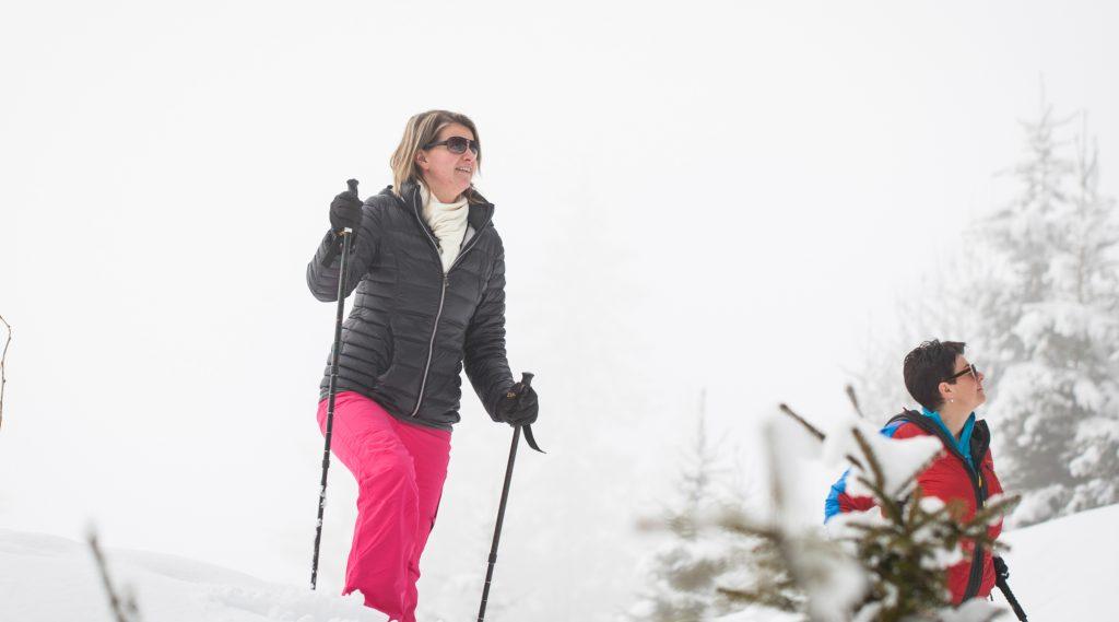 Frau in pinker Schneehose und schwarzer Jacke beim Winterwandern