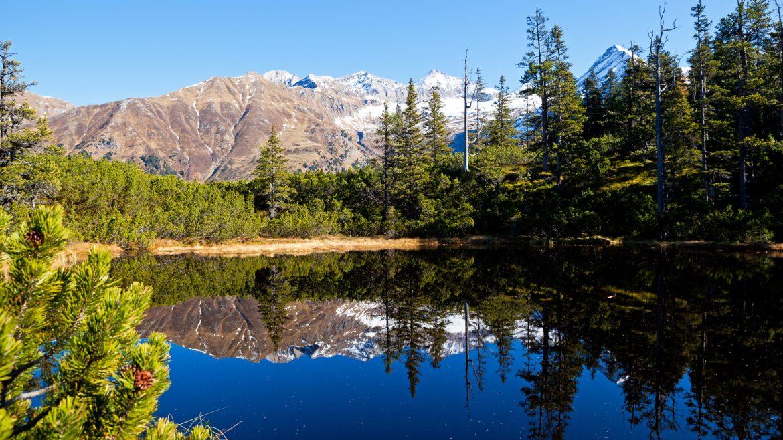 Berge und Bäume spiegeln sich im Bergsee