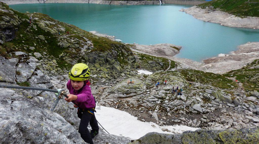 Kind klettert in der Wand, im Hintergrund ist der Weißsee sichtbar