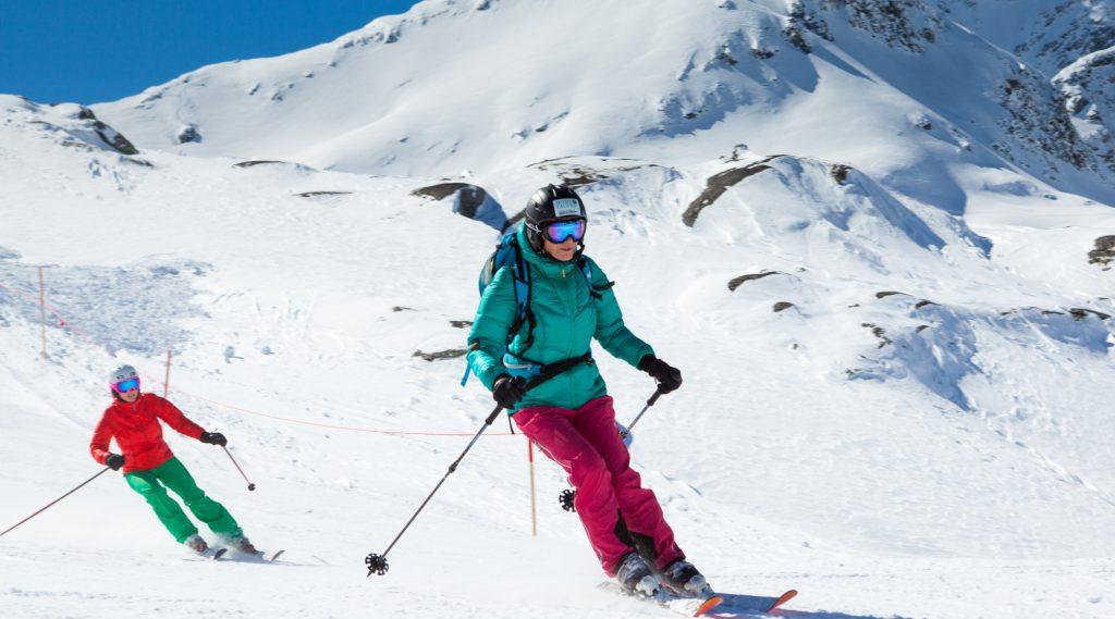 Skifahrer in türkiser Jacke und roter Hose beider Abfahrt