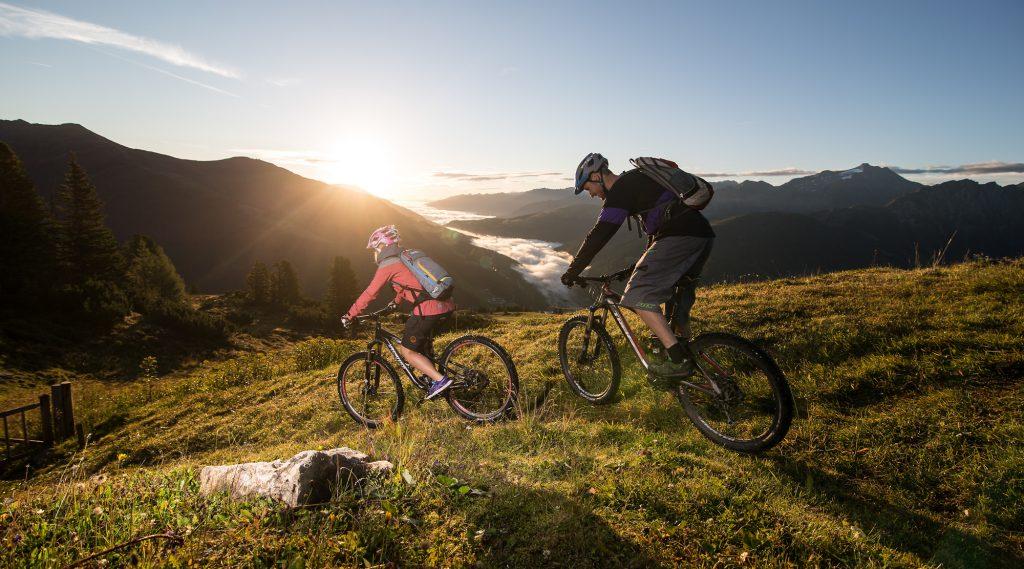 Zwei Mountainbiker im Gegenlicht am Weg nach unten über eine Alm