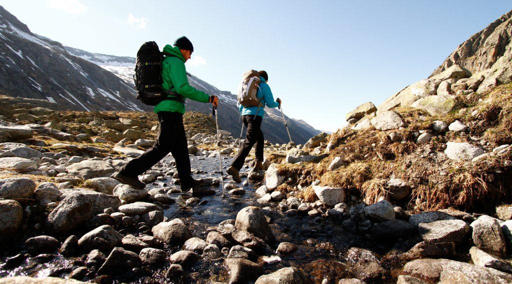 Wandern mit Rucksack und wanderstöcken marschieren durch ein Bachbett