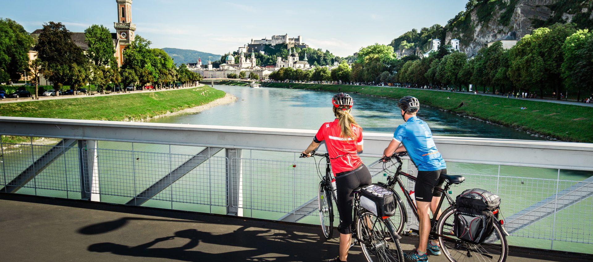 © SalzburgerLand Muellnersteg, zwei Radfahrer blicken zur Festung