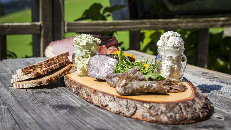 Jause am Holzbrett serviert mit Wurst, Speck und Brot