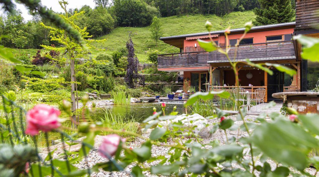 Haus mit Schwimmteich umgeben von einem blühenden Rosengarten, Wiese und Wald